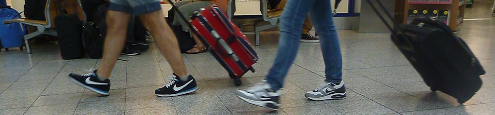 People walking with carry-on luggage at airport